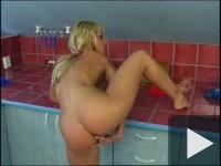 O blondă se masturbează în bucătărie